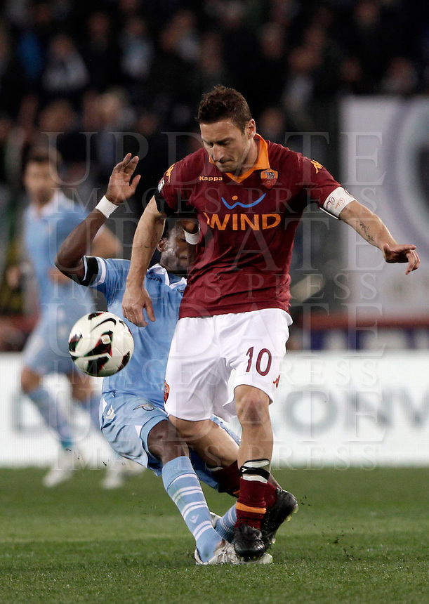 Calcio, Serie A: Roma vs Lazio. Roma, Stadio Olimpico, 8 aprile 2013..AS Roma forward Francesco Totti is challenged by Lazio midfielder Ogenyi Onazi, of Nigeria, partially hidden, during the Italian serie A football match between A.S. Roma  and Lazio at Rome's Olympic stadium, 8 april 2013..UPDATE IMAGES PRESS/Isabella Bonotto
