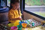 Girl coloring Easter eggs (multi-colors) for kid's Easter Egg hunt, Issaquah, Washington USA  MR.