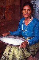 Woman winnowing rice.