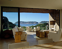 The clean white living area becomes an outdoor room linked as it is to the eucalyptus lined terrace with its niche seating
