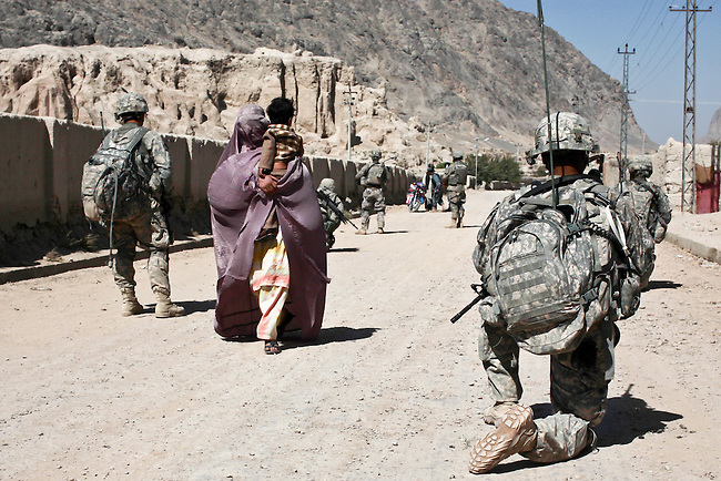 A woman wearing a burqa carries a child through U.S. soldiers from Company D, 1st Battalion, 22nd Infantry Regiment on patrol in the Zor Shar, the old city of Kandahar, Afghanistan. Oct. 7, 2010. DREW BROWN/STARS AND STRIPES