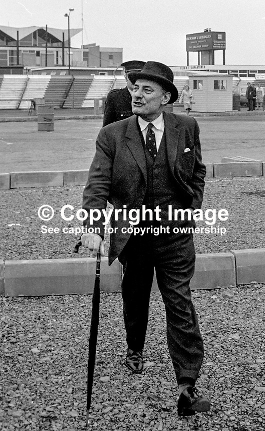 Former UK Conservative MP Enoch Powell, the quintessential Englishman with dark suit, homburg and rolled umbrella arrives at Belfast, N Ireland's Aldergrove Airport amid speculation that he would standing as an Ulster Unionist MP at Westminster for a N Ireland constituency. Considered a possible IRA target he has a policeman in close attendance. 197406000466EP1..Copyright Image from Victor Patterson, 54 Dorchester Park, Belfast, UK, BT9 6RJ..Tel: +44 28 9066 1296.Mob: +44 7802 353836.Voicemail +44 20 8816 7153.Skype: victorpattersonbelfast.Email: victorpatterson@mac.com.Email: victorpatterson@ireland.com (back-up)..IMPORTANT: If you wish to use this image or any other of my images please go to www.victorpatterson.com and click on the Terms & Conditions. Then contact me by email or phone with the reference number(s) of the image(s) concerned.