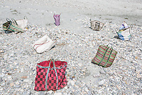 India – West Bengal: Bags belonging to stonecrushers in the Diana riverbed at Red Bank Tea Estate, in the Dooars region. The garden, which houses 888 workers out of a population of 5,000 people, shut down and reopened several times in the past 12 years. It has now been closed since 2013, forcing its workers to resort to stonecrushing in order to survive.