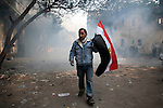 A man leaves an area of Mohamed Mahmoud Street shrouded in tear gas, near Tahrir Square in Cairo, Egypt, Tuesday, November 22, 2011. Clashes between Central Security Forces and demonstrators demanding an end to military rule continued into a fourth day.