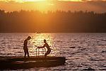 Lake Washington sunset with boys on dock silhouetted Kirkland Washington State USA.