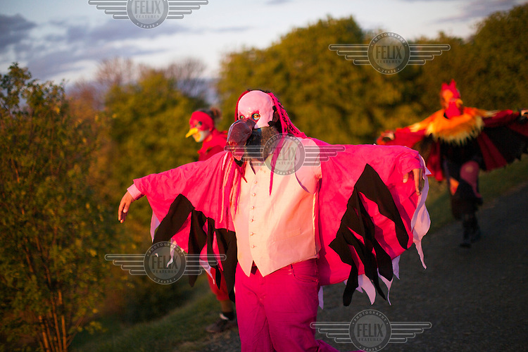A reveller wearing a bird mask and pink 'wings' dances around Carlton Hill in Edinburgh with other participants at the Beltane Fire Festival. The Beltane Festival is an annual event when winter is purged by fire. From sunset on 30 April until early morning, over 300 volunteers create a dramatic reimagining of pagan gaelic folklore surrounded by a crowd of 6000 people. The May Queen arises to herald summer through a battle between elemental forces of order and chaos reaching a climax in the death of the green man in his winter form before bringing him back to life.