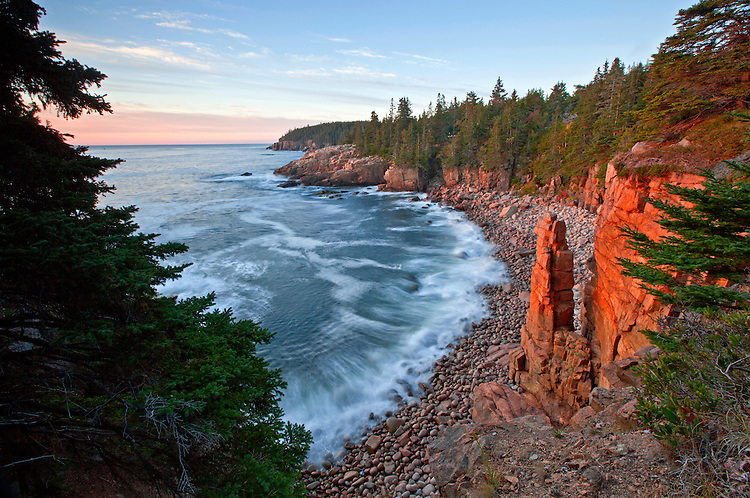 A rock spire soaks up the direct light during a autumn sunrise in Monument Cove at Acadia National Park, Maine, USA
