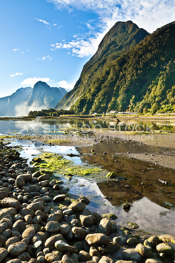 Late afternoon Milford Sound reflection in the late afternoon with sunlit mist rising from Bowen Falls in the distance, Fiordland National Park, South Island, New Zealand - stock photo, canvas, fine art print