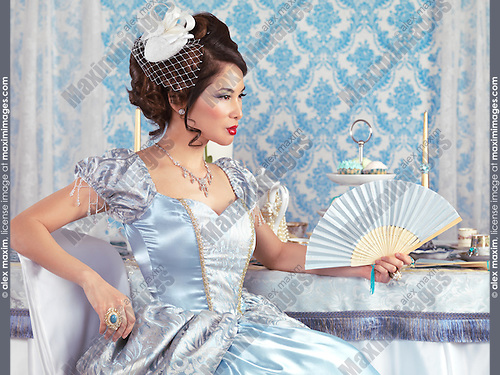 Gorgeous asian lady in a fancy blue princess dress sitting at a tea party table with a fan