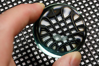 MAGNIFYING LENS OVER MESH SCREEN<br /> Chromatic Aberration Visible At Edge of Lens<br /> A typical magnifying glass consists of a single thin bi-convex lens that produces a modest magnification in the range of 1.5x to 30x. It produce a virtual image that is magnified and upright.