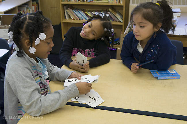 Oakland CA  Second grade students, African American and Latino, studying math flash cards in cooperative learning situation