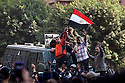 Several protestors and an Egyptian security force officer attempt to calm and dialog with a the larger crowd of protestors from atop a riot police truck during a brief cease-fire that took place in between demonstrations November 21, 2011 near Tahrir square  in central Cairo, Egypt. The cease-fire held for about 15 minutes before returning to pitched street battles. Thousands of protestors demanding the military cede power to a civilian authority clashed with Egyptian security forces for a third straight day in Cairo, with hundreds injured and at least 24 protestors killed.  (Photo by Scott Nelson)