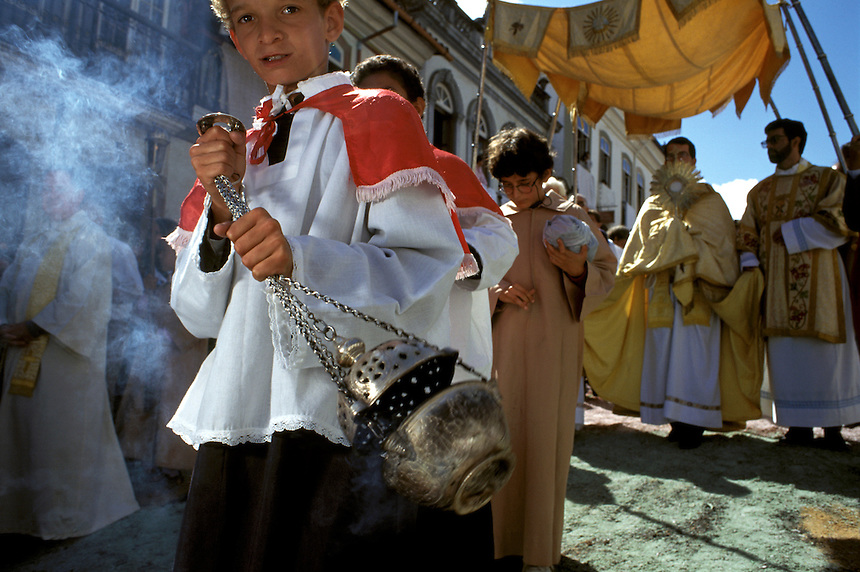 Swinging an incensor, a young altar boy makes way for a local priest carrying the Holy Eucharist during Easter Sunday's procession in Ouro Prêto, Brazil.