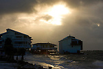 The early morning sun breaks through the storm clouds of Tropical Storm Alberto as waves roll into Cedar Key, Florida June13, 2006. REUTERS/Scott Audette