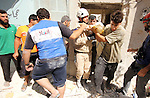Syrian rescue workers carry a body of a man following a reported barrel-bomb attack by Syrian government forces, in the Tariq al-Bab neighbourhood in the northern city of Aleppo, on August 21, 2015. Photo by Ameer al-Halbi
