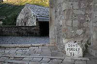 Don't Forget '93, a commemoration stone for the 1993 Siege of Mostar in the Yugoslav Wars, at dawn on the Stari Most or Old Bridge, a 16th century Ottoman bridge across the Neretva river, in Mostar, Bosnia and Herzegovina. The bridge was destroyed in the 1990s Yugoslavian war and has been rebuilt. The town is named after the mostari or bridge keepers of the Old Bridge. Mostar developed in the 15th and 16th centuries as an Ottoman frontier town and is listed as a UNESCO World Heritage Site. Picture by Manuel Cohen