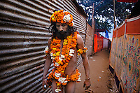 A Naga Sadhu, holding a digicam, walking down the narrow lanes of Juna Akhara during the Kumbh Mela, 2010. Naga Sadhus belong to the Shaiva sect, they have matted locks of hair and their bodies are covered in ashes like Lord Shiva.<br />