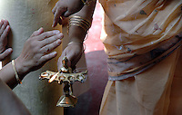 INDIA (West Bengal - Calcutta)  2006, Visitors at Mullick family house (one of the well known families in South Calcutta)take the warmth and the vapour of the oil lamp with which Durga is being worshiped as a symbol of showing respect which may bring prosperity according to Hindu belief . Durga Puja Festival is the biggest festival among bengalies.  As Calcutta is the capital of West Bengal and cultural hub of  the bengali community Durga puja is held with the maximum pomp and vigour. Ritualistic worship, food, drink, new clothes, visiting friends and relatives places and merryment is a part of it. In this festival the hindus worship a ten handed godess riding on a lion armed wth all possible deadly ancient weapons along with her 4 children (Ganesha - God for sucess, Saraswati - Goddess for arts and education, Laxmi - Goddess of wealth and prosperity, Kartikeya - The god of manly hood and beauty). Durga is symbolised as the women power in Indian Mythology.  In Calcutta people from all the religions enjoy these four days of festival in the moth of October. Now the religious festival has become the biggest cultural extravagenza of Calcutta the cultural capital of India. Artistry and craftsmanship can be seen in different sizes and shapes in form of the idol, the interior decor and as well as the pandals erected on the streets, roads and  parks.- Arindam Mukherjee