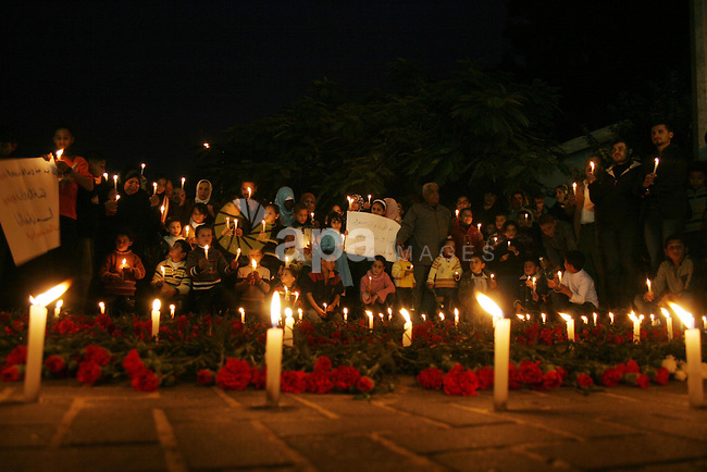 Palestinians take part in a candle light vigil at the UN headquarters in Gaza City December 28, 2009 in support of war widows on the first anniversary of Israel's winter offensive on the territory. The Hamas-ruled enclave is marking one year since the start of Israel's deadliest offensive ever launched on the territory that killed 1,400 Palestinians, including more than 400 minors, and 13 Israelis. Photo by Ashraf Amra