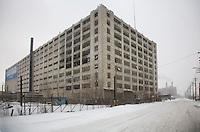 Detroit: paesaggio urbano. Un vecchio e grosso edificio malmesso in una strada innevata. Sullo sfondo due ciminiere fumanti.