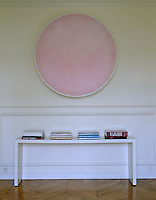 Organised piles of books on a contemporary table below a pink medallion painted on the wall of this corridor