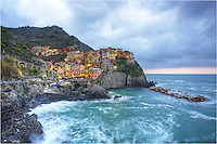 This image of the Cinque Terre - the fishing village of Manarola - was captured early in the morning Some of the lights were still on and a storm was moving out to sea. The low clouds over the Ligurian Sea were thick, but soon would give way to a sunny afternoon. ..The Cinque Terre is one of my favorite places in the world, and views like this never cease to fill me with wonder and admiration of how these folks have lived for thousands of years.