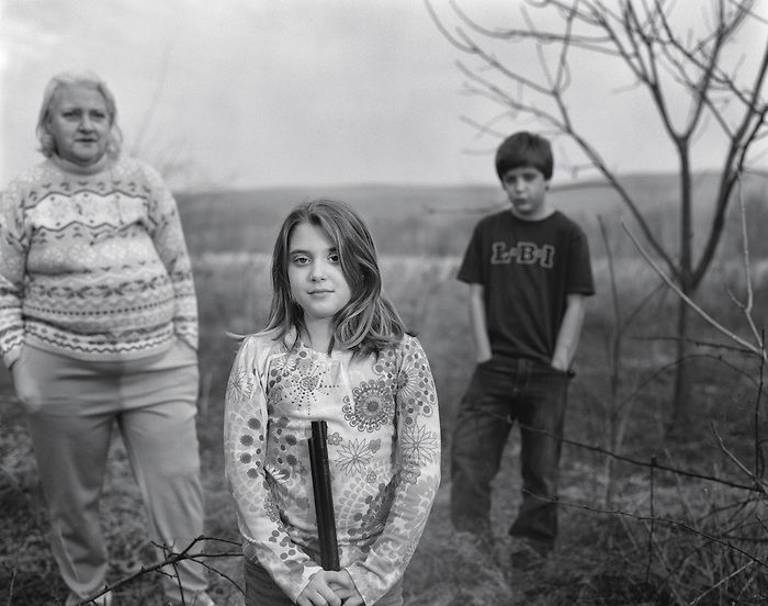 A young girl holding a gun with her brother and grandmother in a field hunting