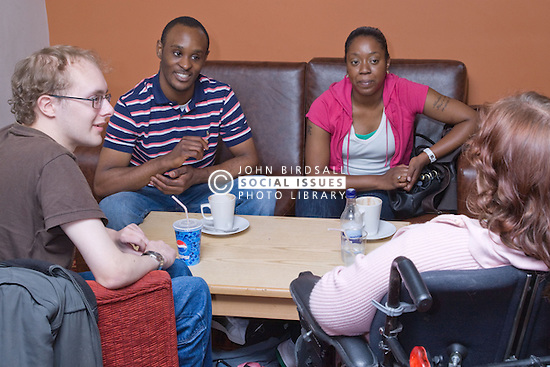 Group of friends; including a young woman who is a wheelchair user; enjoying a drink together,