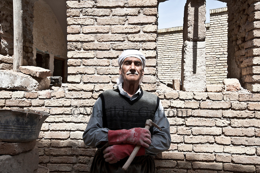 Iraq - Kurdistan - Erbil -   A worker posing in The Citadel. It has been claimed that the site is the oldest continuously inhabited town in the world..The earliest evidence for occupation of the citadel mound dates to the 5th millennium BC, and possibly earlier. It appears for the first time in historical sources during the Ur III period, and gained particular importance during the Neo-Assyrian period. During the Sassanian period and the Abbasid Caliphate, Arbil was an important centre for Christianity. After the Mongols captured the citadel in 1258, the importance of Arbil declined. During the 20th century, the urban structure was significantly modified, as a result of which a number of houses and public buildings were destroyed. In 2007, the High Commission for Erbil Citadel Revitalization (HCECR) was established to oversee the restoration of the citadel. In the same year, all inhabitants, except one family, were evicted from the citadel as part of a large restoration project. Since then, archaeological research and restoration works have been carried out at and around the tell by various international teams and in cooperation with local specialists. The government plans to have 50 families live in the citadel once it is renovated.