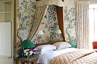A feminine  guest bedroom is decorated with a contemporary Chinese wallpaper