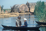 Marsh Arabs. Southern Iraq. Circa 1985.  Children in boats. Reed building on small artificial island called a kibasha. Permanent island called a Dibin.