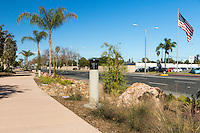 A long view down the Harbor Boulevard Cornerstone Bike Trail in Costa Mesa, California under a clear blue sky highlighting an American flag blowing in the wind at a car dealership across the street.  The landscaping of the path, including a diversity of plants and rocks, can be seen, as can the street and many light posts.  The landscape architecture work on the project was done by David Volz Design.