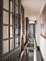 A view into the entrance hallway of a stylish apartment with brown floral pattern curtains at the windows and highly polished floor.