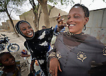 Back home in Timbuktu, Mali, after a year of living in the nation's capital, Bamako, Aissata Kantao (right) jokes with a neighbor. Kantao and her five children fled Timbuktu after the north of Mali was seized by Islamist fighters in 2012. She returned in 2013 several months after it was liberated by French and Malian soldiers, but hasn't found work in the war-torn city.
