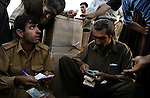 Still on the Iraqi side of the border, Iranian Kurdish smugglers settle up accounts before shouldering the televisions and other electronic goods they will carry from Iraq into Iran on Wed. Sept. 20, 2006.
