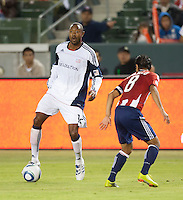 Revolution defender Cory Gibbs (12) looks to pass the ball against Chivas defender Mariano Trujillo (8) during the first half of the game between Chivas USA and the New England Revolution at the Home Depot Center in Carson, CA, on September 10, 2010. Chivas USA 2, New England Revolution 0.