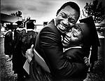 Florida Memorial College student Jerome Robinson gives Debra Pickens a congratulatory hug after graduation ceremonies, 1985.
