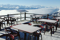Switzerland. Valais. Crans Montana. Winter ski resort. View on the swiss alps from the Bella Lui station ( 2545 meters high). Some ice and snow are still on the tables of the restaurant. The fog is covering the Rhone valley. © 2005 Didier Ruef