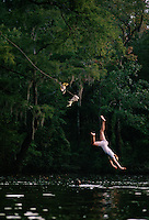 Children jump into the St. Mary's River from a rope swing along the bank in Florida. <br /> Running out of the Okefenokee Swamp, the river has little current as it heads to the Atlantic. <br /> St. Mary's is pristine water for swimming and family canoeing.
