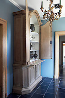 """In the """"Nattier""""-blue entrance hall the interior of an antique oak cupboard has been limewashed to enhance a collection of Khmer vases, Liege glassware and Santa Lucia lanterns"""