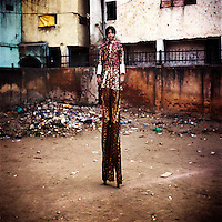 The Tall-Man of the Kathputli Colony. Located in northwest Delhi, Kathputli is inhabited by approximately 2,000 performing artists, practicing traditional art forms such as marionette puppetry, juggling, magic, acrobatics, dance and music. Many have travelled all over the world showcasing their abilities, but they still choose to remain living in this slum, which is one of the most impoverished in the city.