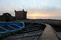 ESSAOUIRA, MOROCCO - MAY 8 : A low angle view of boats at sunset on May 8, 2009 in Essaouira, Morocco. In the background are the Portuguese Tower and Ramparts. On the windswept Atlantic coast of Morocco, Essaouira was re-built in the 18th century by French architect Theodore Cornut to the orders of Sultan Ben Abdullah. Surrounded by ramparts it is a charming small town now becoming more popular with tourists. (Photo by Manuel Cohen)