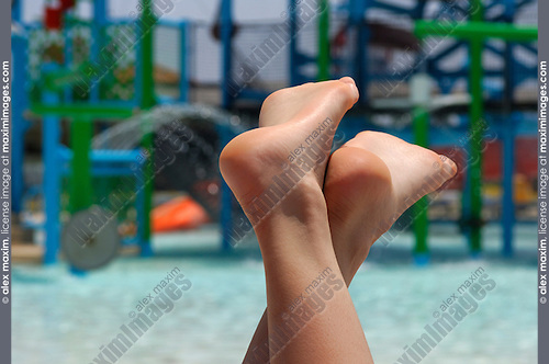Bare feet of young woman relaxing on sunbed near a pool in a water park