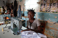 Parakou,Benin. December 2009.  Rose (16) works at her uncle, Obed Ahlinkou's, tailoring shop. She is one of 6 children from a village 250 km south from Parakou. Her uncle brought her to town but prior to that she has never been in a school. In Benin the challenge is to ensure that working children continue their education.  A local NGO, GRADH, asssists in getting working children educated. They negotiate with parents/bosses to let them come to classes. This class has 15 regular students.