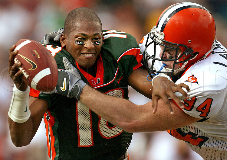 Skin Head--11/15/03 --Miami--University of Miami quarterback Derrick Crudup attempts to break away Syracuse's Ryan LaCasse after loosing his helmet in the fourth quarter at the Orange Bowl.