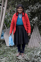 An Andean woman adjacent to the Interoceanic Highway. The dust from the passing trucks can be seen on the surrounding foliage.