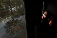 A woman holds her head as she travels on a train through flooded area in Bangkok November 3, 2011. As waterlogged Thailand struggles to contain the worst floods in decades, it faces a simple truth: not a whole lot can be done to avoid a repeat disaster in the short term even with a new multi-billion dollar water-management policy.  REUTERS/Damir Sagolj (THAILAND)