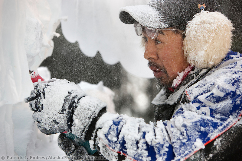 """Japanese ice sculptor Junichi Nakamura, carves away on a single block, realistic sculpture titled """"Surfacing Kingfisher"""" during the 2009 World Ice Art Championships in Fairbanks, Alaska."""