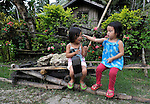 """Two girls play in Nalapaan, one of seven villages near Pikit which has declared itself a """"space for peace."""" An initiative of the Immaculate Conception Parish in Pikit, the spaces for peace are villages where residents have told both the Moro Islamic Liberation Front and the Philippine military to desist from activity within the community. Residents also studied peacebuilding and conflict resolution,  and have made special efforts to increase interfaith dialogue and harmony."""