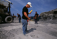 Mine workers load explosives into the earth to break up rock which will expose seams of coal.